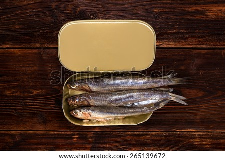 Sardines in can on old wooden textured background with lemon piece. Culinary healthy fish eating. - stock photo