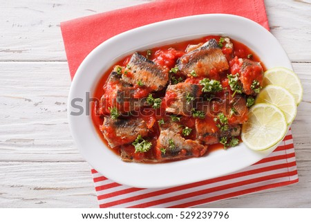 sardines in tomato sauce, decorated with lime and parsley close-up on a plate. horizontal view from above