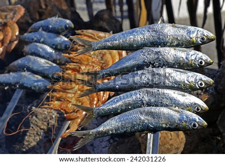 Sardines on a skewer firewood at the beach  - stock photo