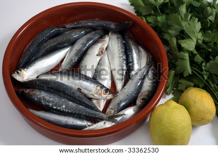 Sardines (pilchards) in a rustic bowl with their heads and innards removed and lemon and parsley beside them. Sardines, are high in Omega-3 oils and Vitamin D - stock photo