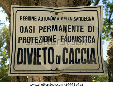 SARDINIA, ITALY - SEPTEMBER 01, 2009: A sign affixed to a tree in a rural part of Sardinia, announcing that hunting is banned in that area because it is a wildlife protection zone.