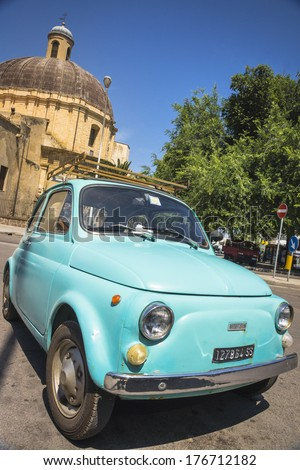 SASSARI, ITALY - JULY 7, 2013: an aqua-colored old Fiat 500 in the second city of Sardinia, Santa Maria Church in the background. The popular and compact Fiat 500 was produced between 1957 and 1975.