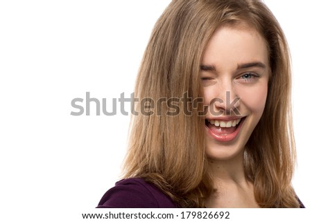 Sassy young woman giving a mischievous wink while laughing and flirting with the camera, face portrait isolated on white with copyspace
