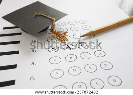 SAT test with pencil and mortar board graduation cap                                - stock photo