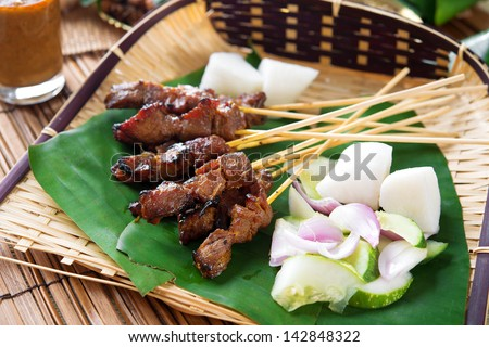 Satay or sate, skewered and grilled meat, served with peanut sauce, cucumber and ketupat, Malaysia or Indonesia food. Traditional Malay food. Hot and spicy Malaysian dish, Asian cuisine. - stock photo