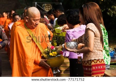 Satchanalai District. Sukhothai, THAILAND - APRIL 13: Thai people celebrate Songkran festival (water festival) in Satchanalai District. Sukhothai, Thailand on April 13, 2011. Offer food to monks. - stock photo