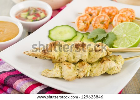 Sate Gai & Sate Goong - Thai chicken and prawn satays served with cucumber and onion relish and peanut sauce. - stock photo