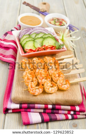 Sate Goong - Thai prawn satays served with cucumber and onion relish and peanut sauce. Side dish of cucumber, red onions and chili. - stock photo