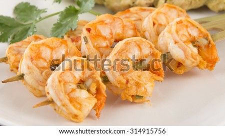Sate Goong - Thai prawn satays served with peanut sauce. Close up.