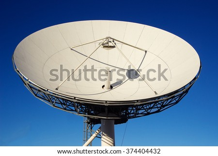Satellite dish antenna on blue sky background.Satellite dish antenna view below - stock photo