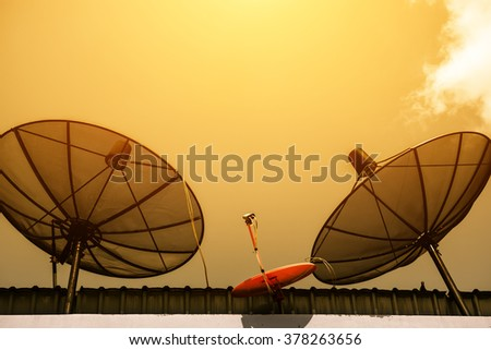 Satellite dish antenna on the roof at sunset time - stock photo