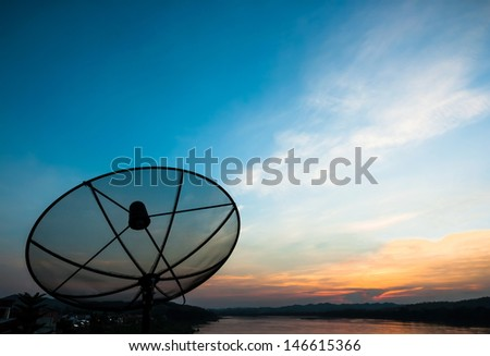 Satellite dish near the river at sunset