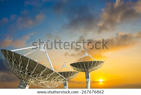 Satellite dish receiving data signal for communication, on colorful sunset sky - stock photo