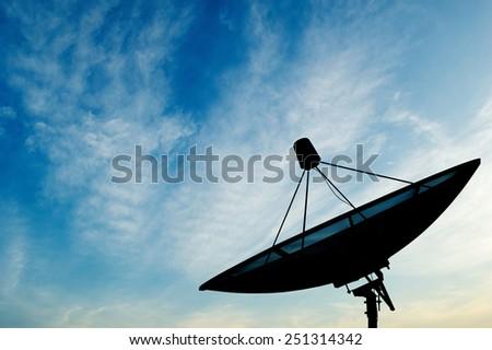 Satellite dish transmission data on blue sky background - stock photo
