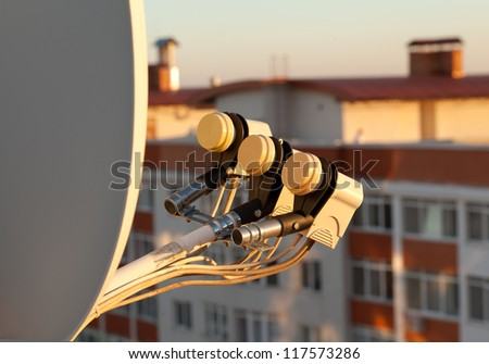 Satellite dish with LNB downconverters. Evening. Residential  background buildings - stock photo