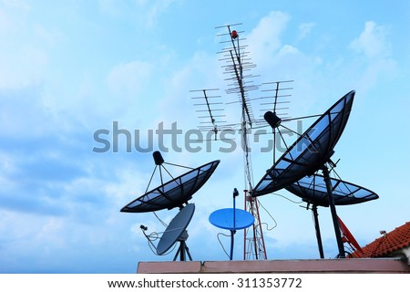Satellite Dishes and TV antennas on the house roof with a beautiful blue sky - stock photo