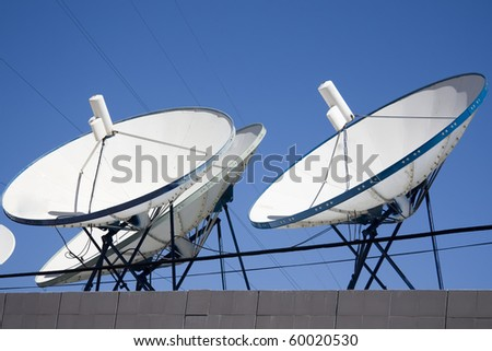 satellite dishes, cables and blue sky background - stock photo