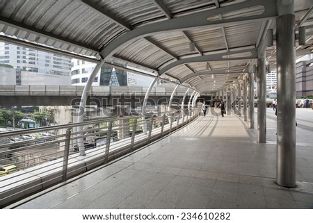 SATHORN ROAD, BANGKOK - NOV 21, 2014: High-Rise buildings and a sky walk at Sathorn-Narathiwas intersection in Bangkok,Thailand. Sky walk is the connecting walkway between sky train and rapid bus.