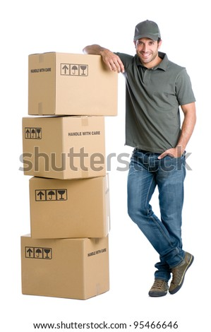 Satisfied and proud delivery man leaning on a stack of boxes isolated on white background - stock photo