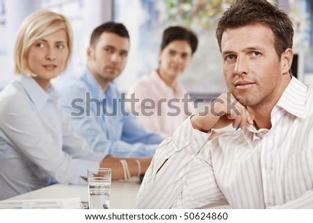 Satisfied businessman sitting at table in meeting room at office, looking at camera. - stock photo