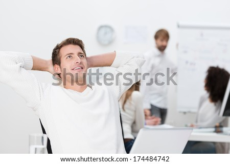 Satisfied businessman taking a break relaxing leaning back in his seat with his hands behind his head looking upwards with a pleased smile - stock photo