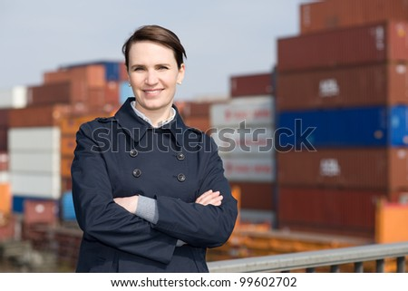 Satisfied businesswoman in front of cargo container terminal