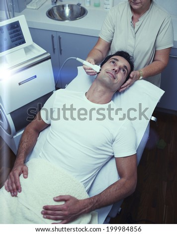 Satisfied customer smiling in having laser treatment at beauty clinic, laser procedure at the  professional and beauty salon  - stock photo