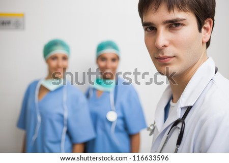 Satisfied doctor wearing labcoat with two smiling nurses wearing scrubs in background in hospital - stock photo