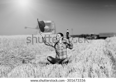 Satisfied farmer girl sitting on harvested field, holding beer in bottle and throwing cowboy hat. Combine harvester working in background. Black and white image - stock photo