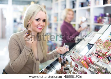 Satisfied female customer buying skin powder in makeup section