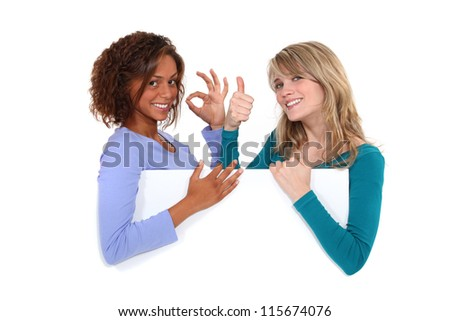 Satisfied girls behind white board - stock photo