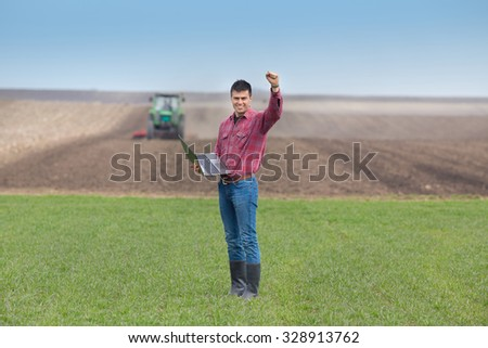 Satisfied landowner with laptop  holding fist up in the air on farmland, tractor plowing in background - stock photo
