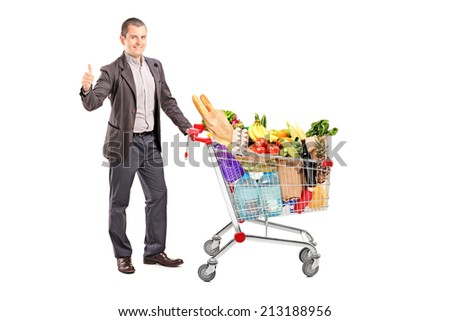 Satisfied man with a cart full of groceries isolated on white background - stock photo