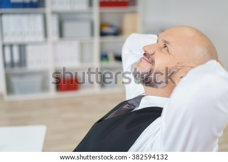 Satisfied mature business man in necktie looking up with hands behind his head in office - stock photo