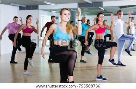 satisfied men and ladies dancing aerobics at lesson in the dance class