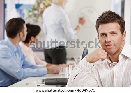 Satisfied mid-adult businessman in business meeting at office, looking at camera smiling. - stock photo