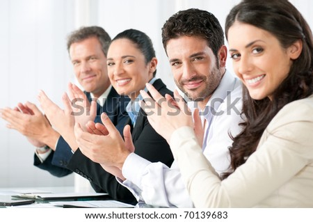 Satisfied proud business team clapping hands and looking at camera in a modern office - stock photo