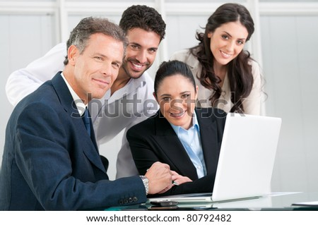 Satisfied proud business team looking at camera and smiling in office - stock photo