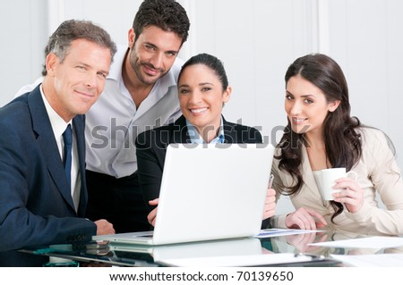 Satisfied proud businss team looking at camera and smiling in office - stock photo