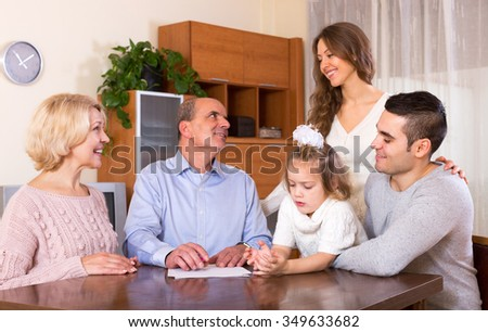 Satisfied relatives sitting at the table and discussing finances at home - stock photo