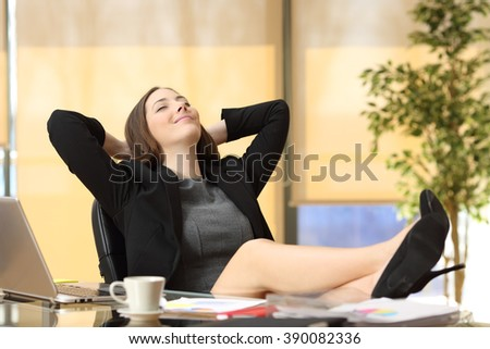 Satisfied relaxed businesswoman sitting in a chair with legs over the table and hands in the head enjoying her new job at office