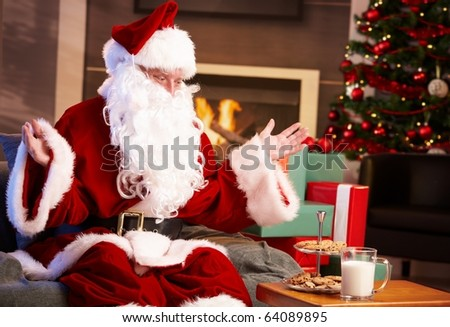 Satisfied Santa Claus sitting at fireplace happy to get milk and chocolate chip cookies.? - stock photo