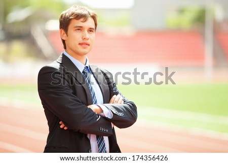 Satisfied smiling businessman standing in the summer outdoors. - stock photo