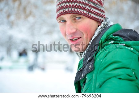 Satisfied smiling businessman standing in the white outdoors. Looking at camera in winter park and smiling - stock photo