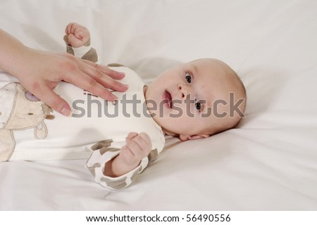 satisfied supine baby in the dress with the hand we have cows - stock photo