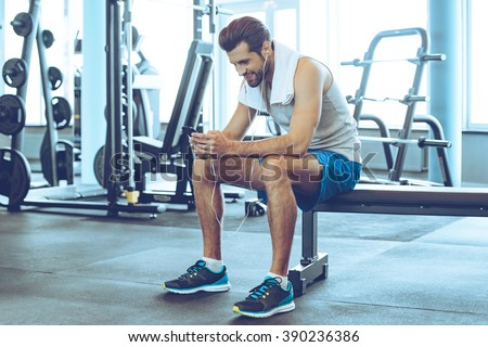 Satisfied with his work out. Handsome young men in headphones using his smart phone with smile while sitting at gym - stock photo