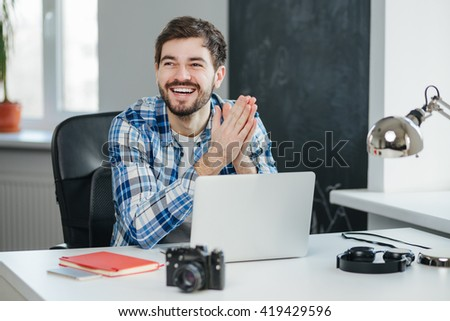 Satisfied with the work done. Cheerful businessman in casual clothes sitting at his desk in the office with laptop. - stock photo