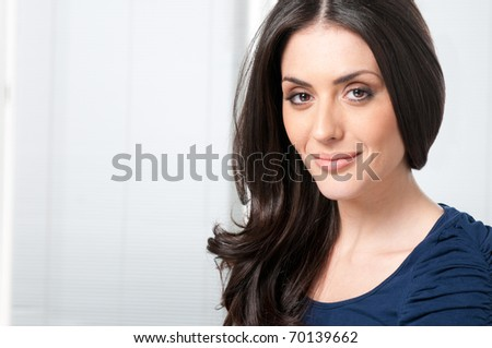 Satisfied young beautiful lady looking at camera and smiling - stock photo