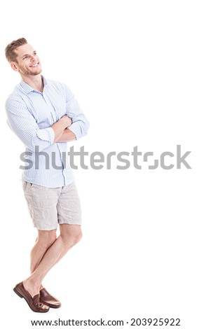 Satisfied young man looking at empty space - full length shot isolated on white background - stock photo