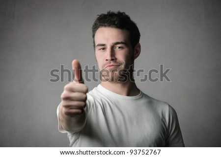 Satisfied young man with thumbs up - stock photo